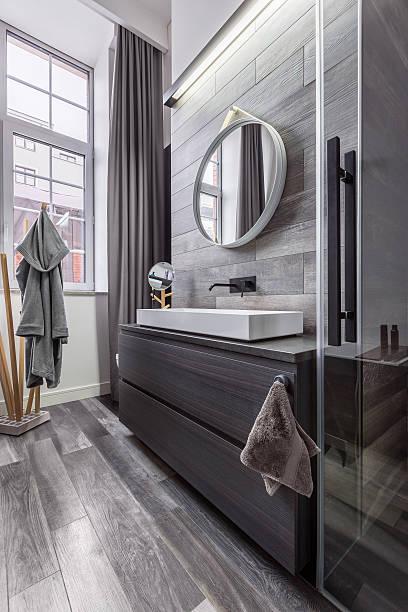 wooden bathroom with round mirror - badezimmermöbel holz stock-fotos und bilder