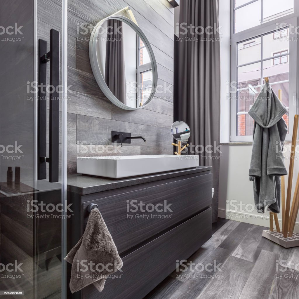 Wooden bathroom with round mirror stock photo