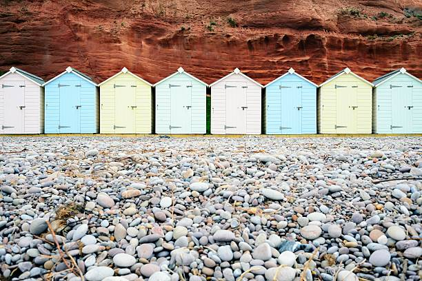 Wooden Beach Huts A row of pastel coloured beach huts on the pebble beach at Budleigh Salterton in southwest England. beach hut stock pictures, royalty-free photos & images