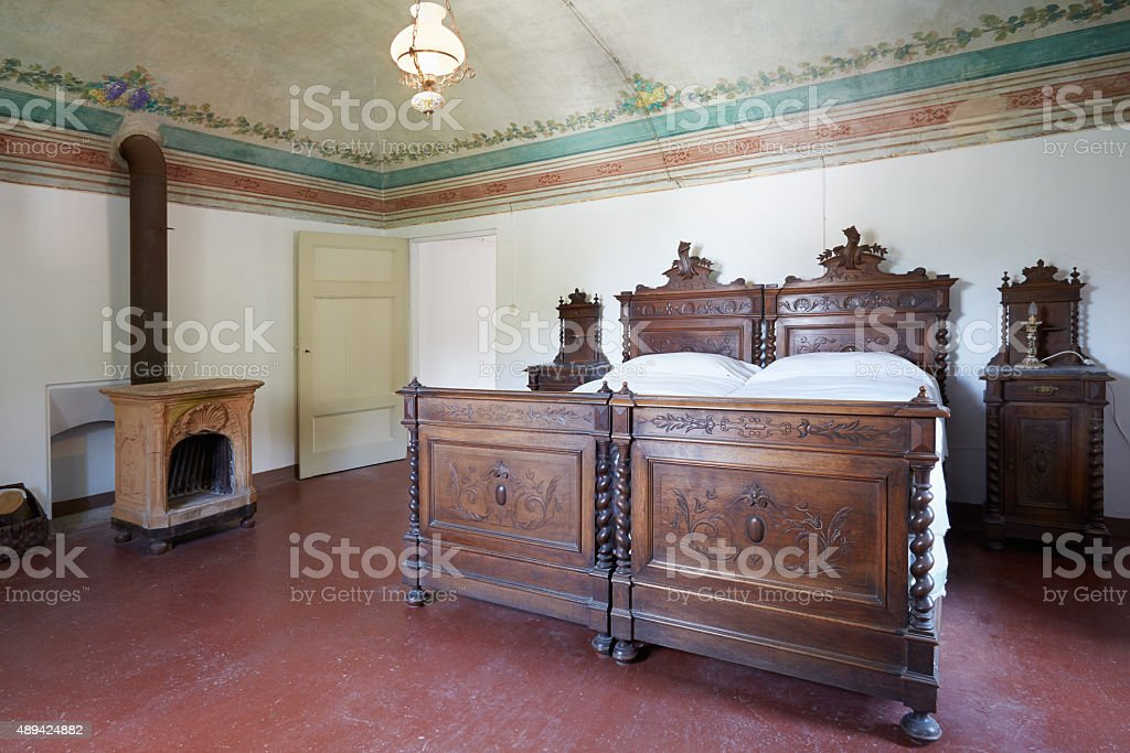 Wooden bedroom in ancient house with floral fresco stock photo