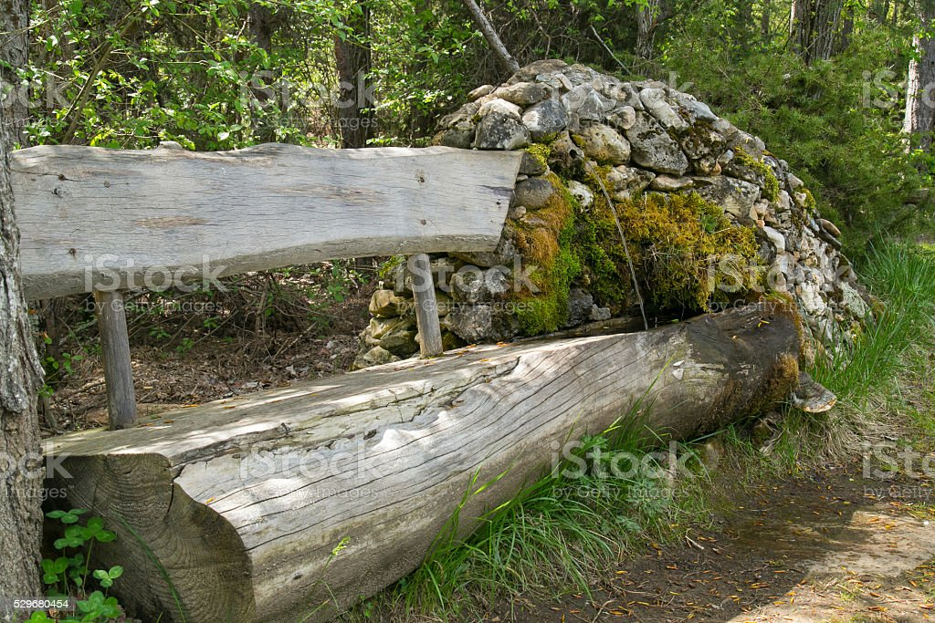 Wooden bench and a stone fountain stock photo