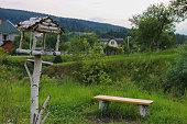 Wooden bench and birdhouse in Carpathians, Ukraine