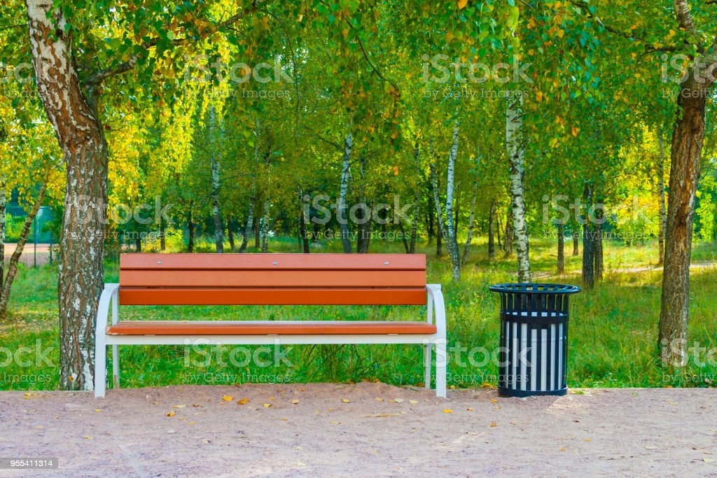 Wooden bench and metal black trash can in the park on a background of green trees - Zbiór zdjęć royalty-free (Bez ludzi)