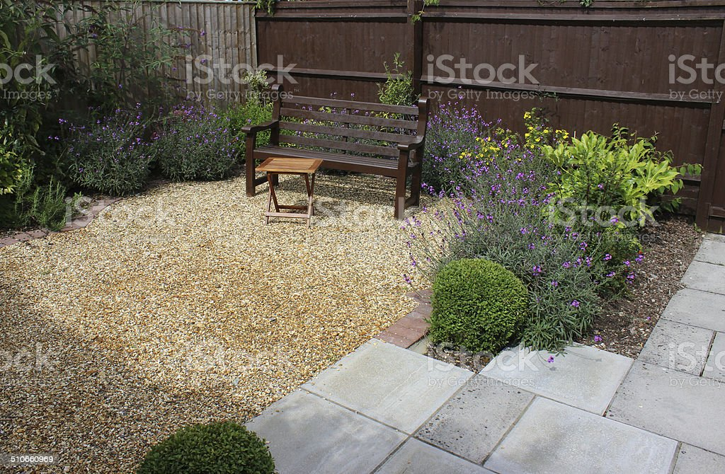Wooden bench in gravel garden with flowers, shrubs, fence, table stock photo