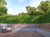 Wooden bench in the garden 3d render,  There is a wooden floor terrace,green bush fence,decorate with wood and white fabric furniture.