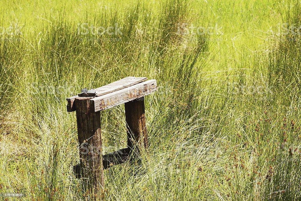 Wooden Bench Post Grass Field stock photo
