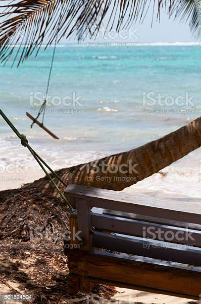 Wooden bench swing next to a palm tree in front picture id501824504?b=1&k=6&m=501824504&s=612x612&h=vjb4il7thww 29rb9ltgkhs zwmiktfs2f5zfctxfa4=
