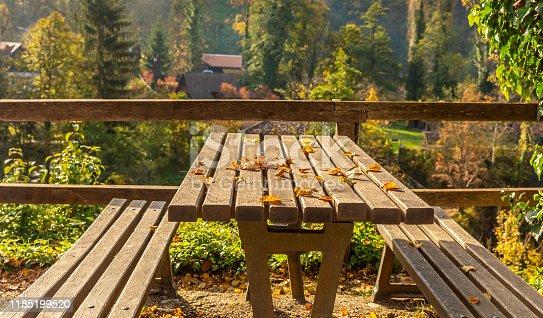 989111446 istock photo wooden bench  with yellow foliage in autumn. Autumn scene 1185199520