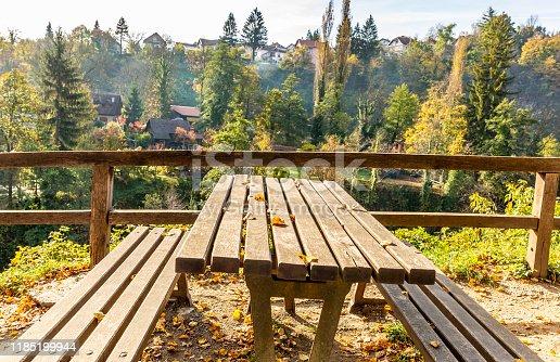 989111446 istock photo wooden bench  with yellow foliage in autumn. Autumn scene 1185199944