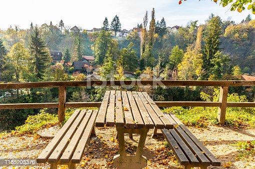 989111446 istock photo wooden bench  with yellow foliage in autumn. Autumn scene 1185203376