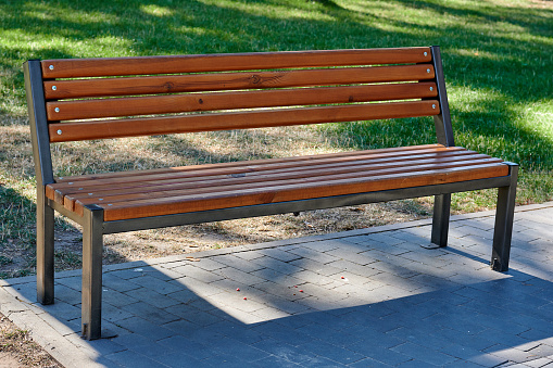 A wooden bench without people stands in a city park. High quality photo
