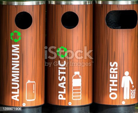 Wooden garbage tin cans labelled in plastics, aluminum, and general waste