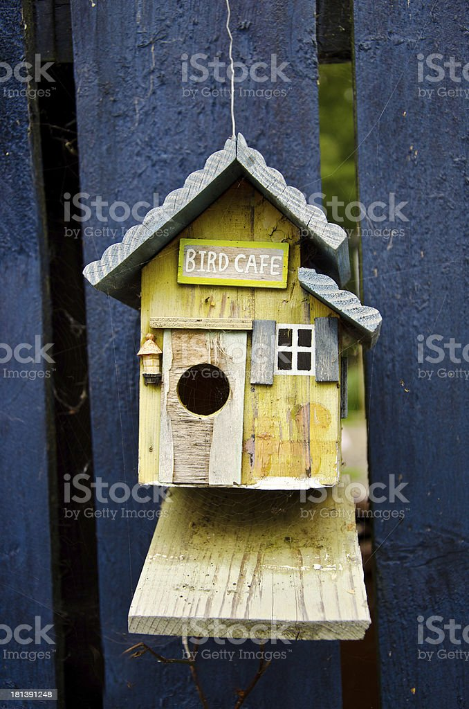 Wooden birdhouse called on blue fence royalty-free stock photo