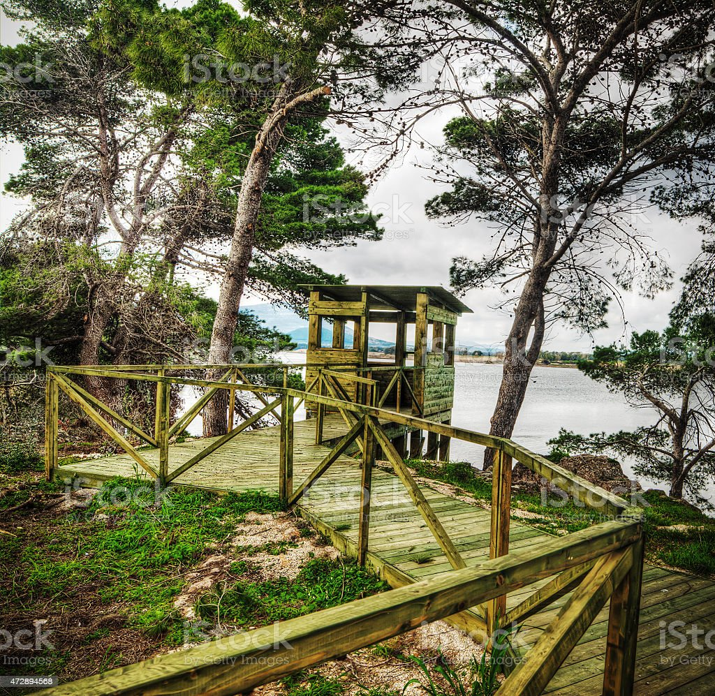 wooden birdwatching cabin by the water stock photo