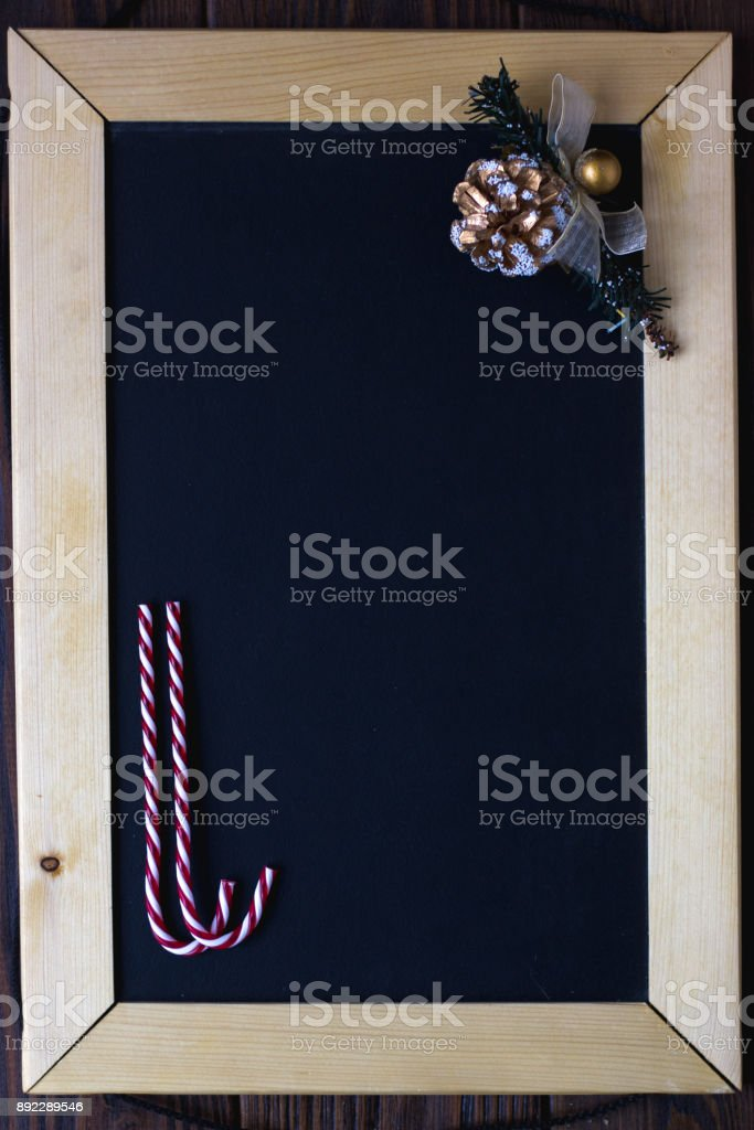 Wooden blackboard with place for your text with christmas candys and fir-cone. stock photo
