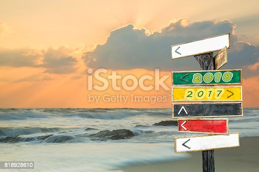 istock Wooden blank sign with text 2018 and 2017 with sunrise beach background 818928610