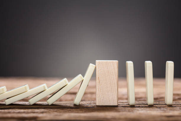 Wooden Block Amidst Falling And Upright Domino Pieces On Table stock photo
