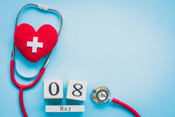 Wooden Block calendar for World Red Cross and Red Crescent day, May 8. Healthcare and medical concept. Red heart with Stethoscope on blue background. stock photo