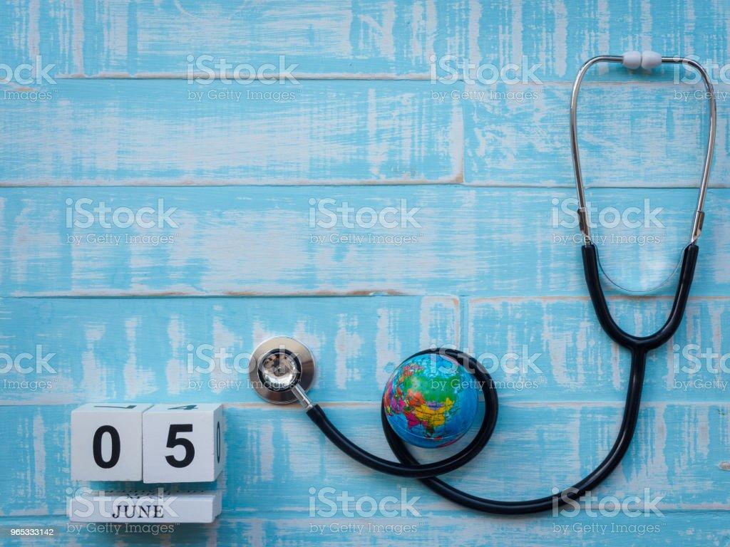 6月05日木塊日曆地球儀和聽診器在藍色木質背景。 - 免版稅一起圖庫照片