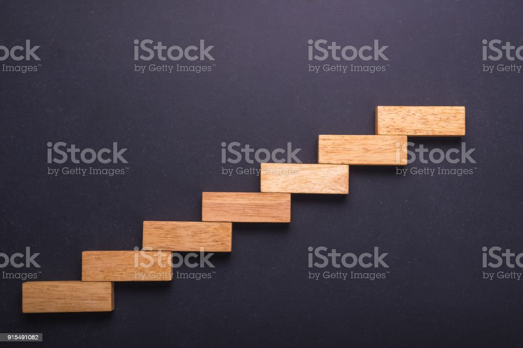Wooden block set up for staircase on black stone board. Business concept for growth success process. stock photo