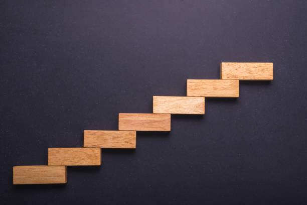 Bloque de madera para escalera en piedra pizarra. Concepto de negocio para el proceso de éxito de crecimiento. - foto de stock