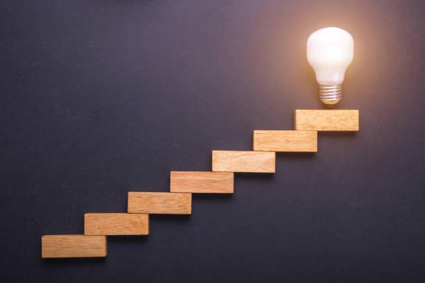 木製のブロックは、ブラック ボードに石上のトップ ポイントに電球と階段用を設定しました。ビジネスの成功のアイデア コンセプトを作成し、 - ステップ ストックフォトと画像