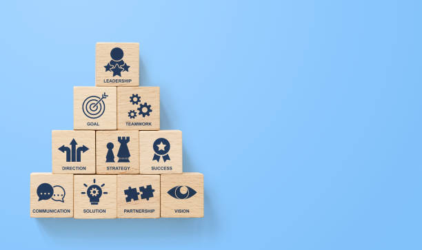 Pirámide de apilamiento de bloques de madera con negocios líderes de icono sobre fondo azul. Factores clave de éxito para el concepto de elementos de liderazgo - foto de stock