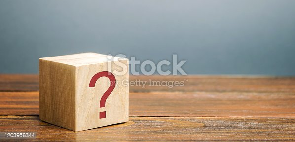Wooden block with a question mark. Asking questions, searching for truth. Riddle mystery, investigation and research. FAQ - frequently asked questions. Search for information. Q&A