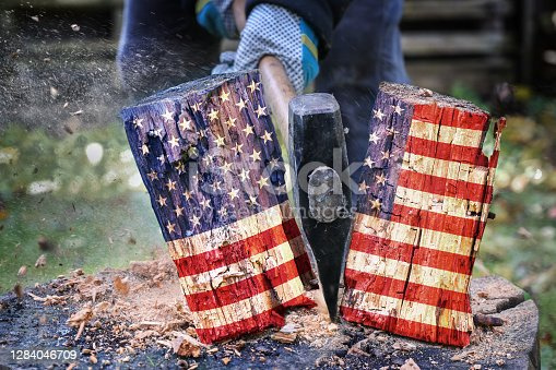 istock Wooden block with American flag is split in two halves with an axe, metaphor for the divided country after the election 1284046709