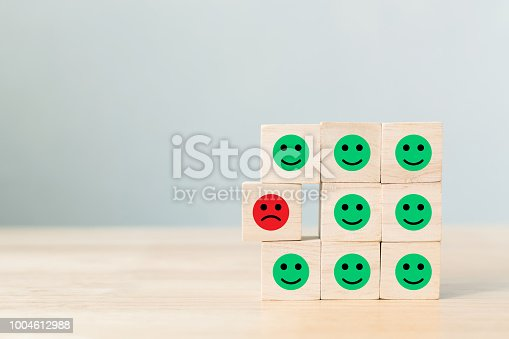 Wooden block with icon face emotion happiness and sadness, Unique, think different, individual and standing out from the crowd concept