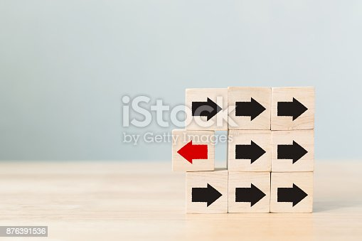 istock Wooden block with red arrow facing the opposite direction black arrows, Unique, think different, individual and standing out from the crowd concept 876391536