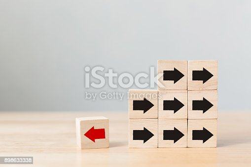 istock Wooden block with red arrow facing the opposite direction black arrows, Unique, think different, individual and standing out from the crowd concept 898633338