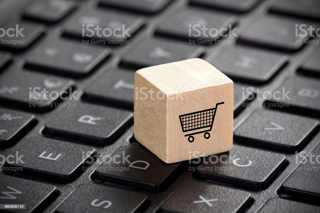 Wooden block with shopping cart graphic on laptop keyboard stock photo