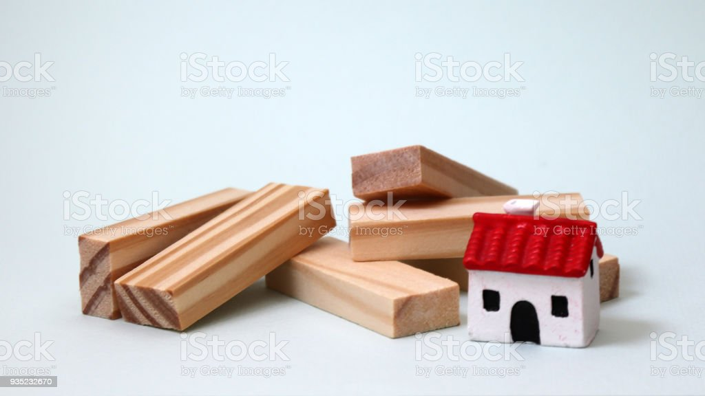 wooden blocks and a miniature house of red roof stock photo