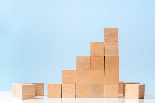 Wooden blocks as increasing graph bar on blue background