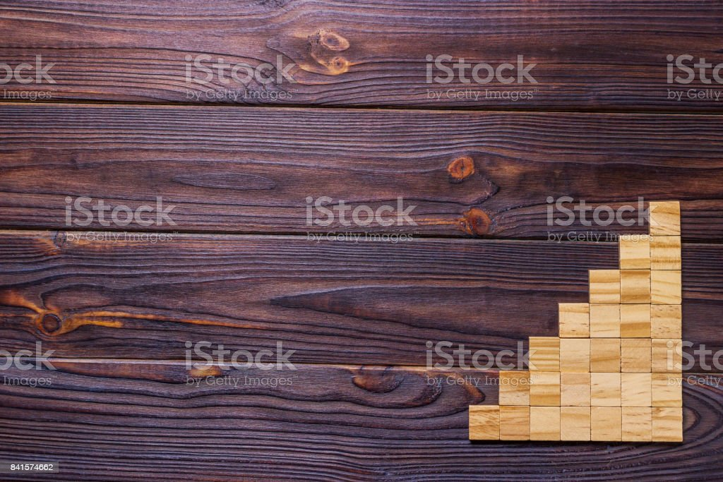 A wooden blocks cube over black wooden textured background with copy space for add word text title. Concept or conceptual Wood block stair or seven steps. Cubic. stock photo