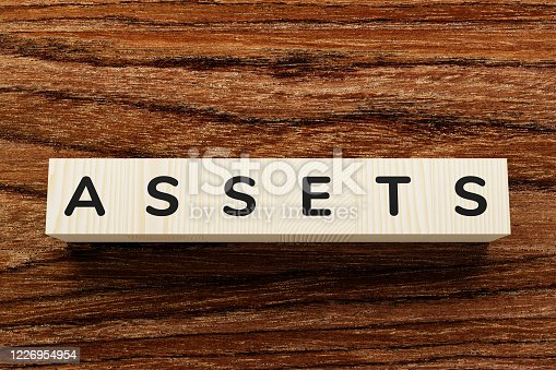 Business success concept, word assets on wooden background. Wooden blocks with letters on them.
