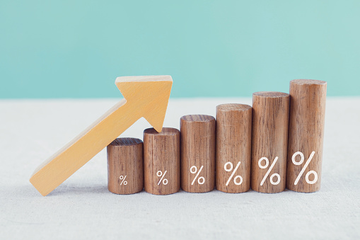 Wooden blocks with percentage sign and arrow up, financial growth, interest rate and mortgage rate increase, inflation concept
