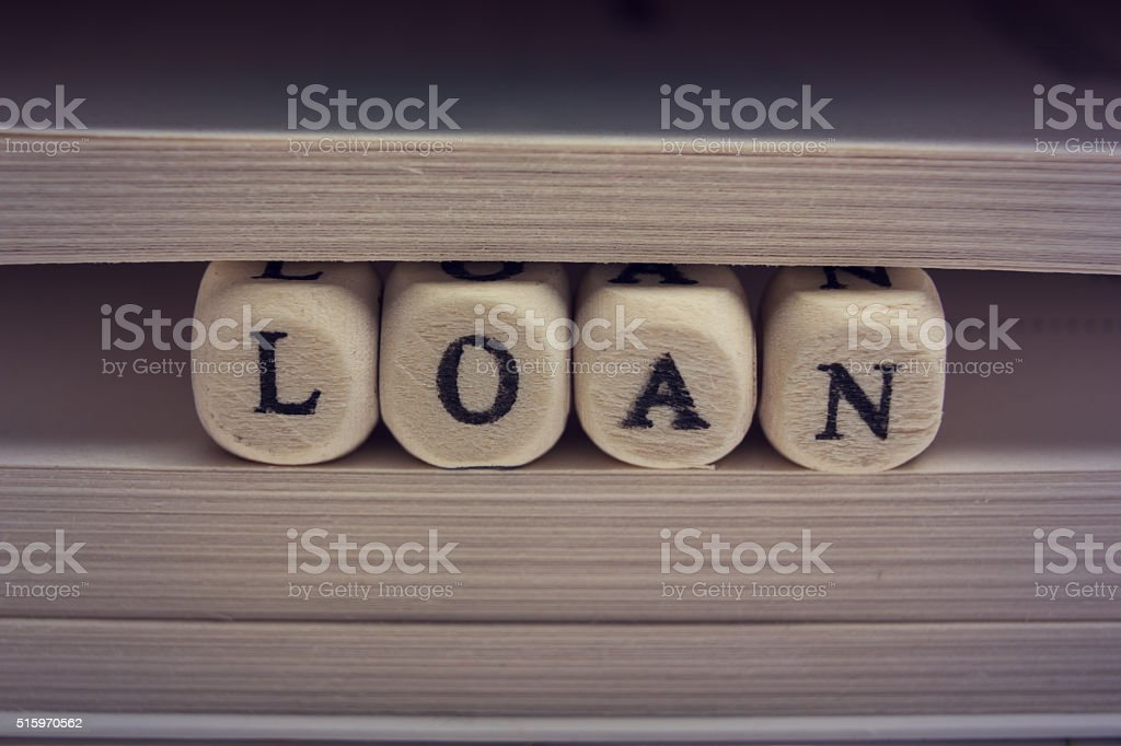 Wooden Blocks with text Loan and book pages stock photo