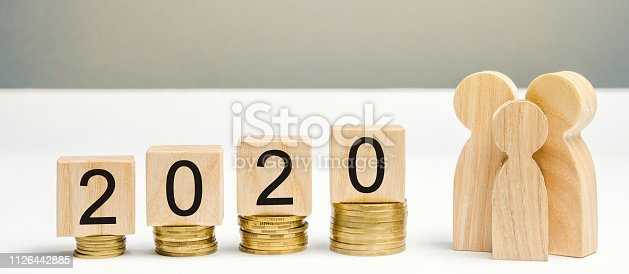 1170746979istockphoto Wooden blocks with the word 2020, coins and family. Concept of saving money for the future. Budget planning for 2020. Investing. Favorable money distribution. Profit. Income. Salary. Cash 1126442885