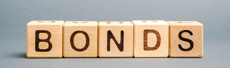 Wooden blocks with the word Bonds. A bond is a security that indicates that the investor has provided a loan to the issuer. Equivalent loan. Unsecured and secured bonds