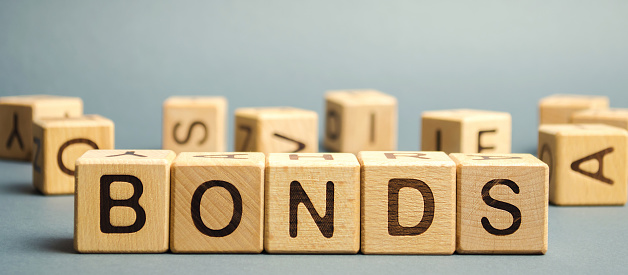 Wooden blocks with the word Bonds. A bond is a security that indicates that the investor has provided a loan to the issuer. Equivalent loan. Unsecured, secured bonds. Business and finance