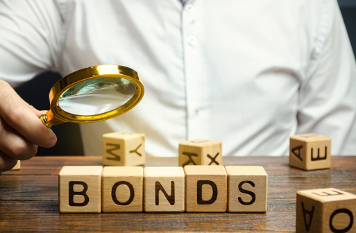 Wooden blocks with the word Bonds and businessman. A bond is a security that indicates that the investor has provided a loan to the issuer. Equivalent loan. Unsecured and secured bonds.