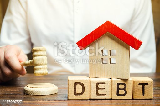 612372074istockphoto Wooden blocks with the word Debt and a miniature house with a judge's hammer. Confiscation of property for failure to pay the debt. The withdrawal of housing. Moratorium. Criminal penalty 1137020727