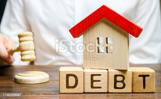 612372074 istock photo Wooden blocks with the word Debt and a miniature house with a judge's hammer. Confiscation of property for failure to pay the debt. The withdrawal of housing. Moratorium. Criminal penalty 1140129467