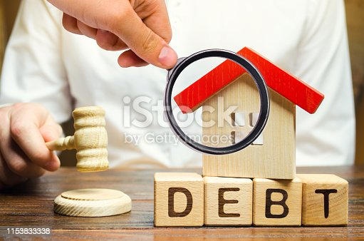 612372074 istock photo Wooden blocks with the word Debt and a miniature house with a judge's hammer. Confiscation of property for failure to pay the debt. The withdrawal of housing. Moratorium. Criminal penalty 1153833338