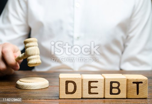 612372074 istock photo Wooden blocks with the word Debt and judge with a gavel. The concept of judicial punishment for non-payment of debt. Property debts. Tax evasion / avoidance. Bankruptcy and financial crisis 1140129402