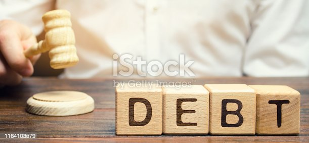 612372074 istock photo Wooden blocks with the word Debt and judge with a gavel. The concept of judicial punishment for non-payment of debt. Property debts. Tax evasion / avoidance. Bankruptcy and financial crisis 1164103579