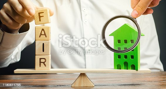 Wooden blocks with the word Fair and a wooden house. Fair value of real estate and housing. Property valuation. Home appraisal. Housing evaluator. Legal transparent deal. Apartment purchase / sale.