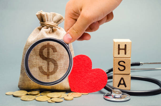 wooden blocks with the word hsa and money bag with stethoscope. health savings account. health care. health insurance. investments. tax-free medical expenses. coins and dollar sign. red heart - commercial activity stock photos and pictures